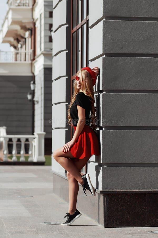 Retrato de la mujer rubia joven hermosa que lleva el equipo negro elegante, ella que sonr?e en fondo urbano fotos de archivo