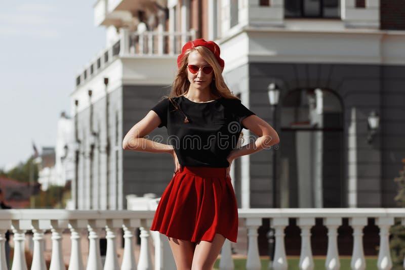 Retrato de la mujer rubia joven hermosa que lleva el equipo negro elegante, ella que sonr?e en fondo urbano fotografía de archivo