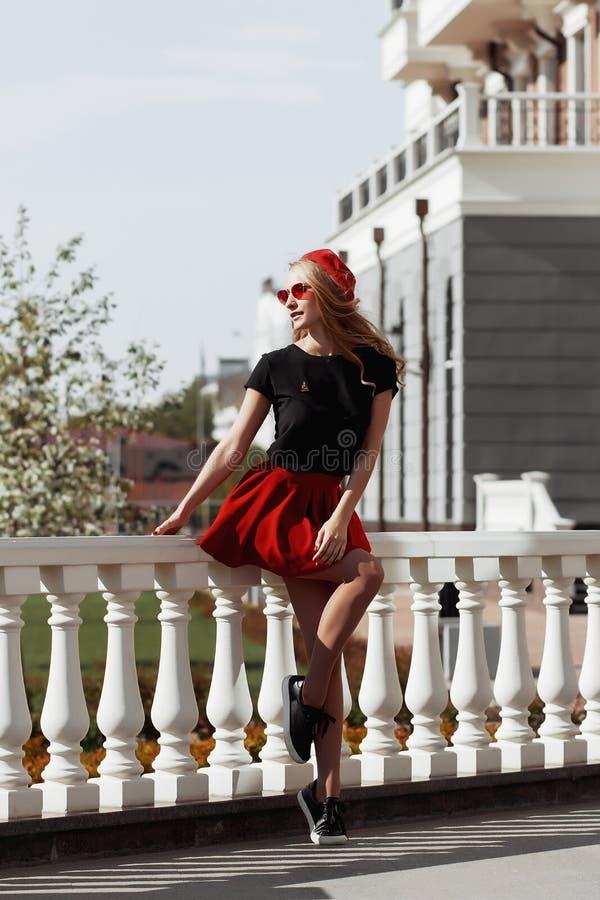 Retrato de la mujer rubia joven hermosa que lleva el equipo negro elegante, ella que sonr?e en fondo urbano foto de archivo
