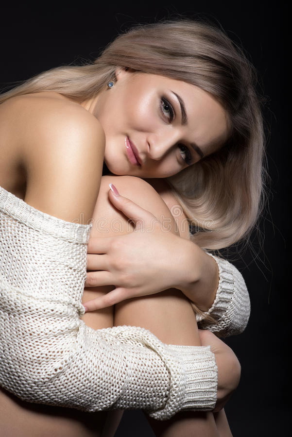 Retrato de la mujer rubia joven hermosa que se sienta abrazando su kne imagen de archivo libre de regalías