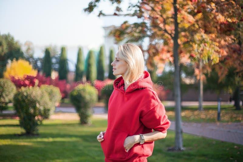 Retrato de la mujer rubia joven que se está colocando en el parque Ella se está enfriando hacia fuera fotos de archivo libres de regalías