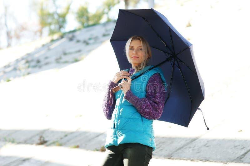 Retrato de la mujer rubia madura preciosa smilling feliz con el paraguas imagen de archivo