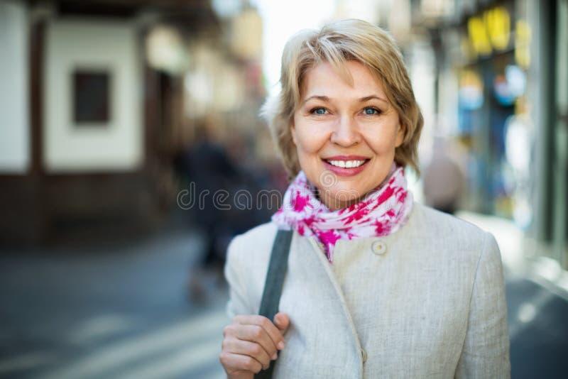 Retrato de la mujer rubia madura sonriente en ciudad foto de archivo libre de regalías