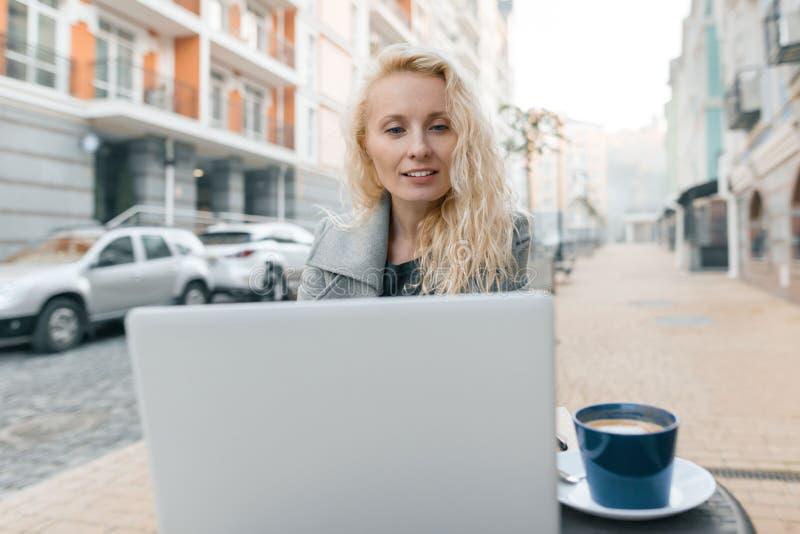 Retrato de la mujer rubia de moda hermosa joven en la ropa caliente que se sienta en un café al aire libre con el ordenador portá fotos de archivo libres de regalías