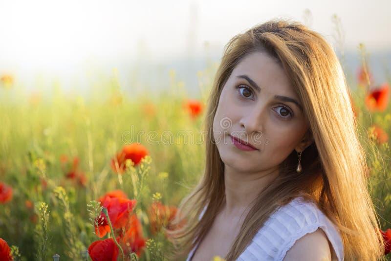 Retrato de la mujer rubia que se coloca en el campo de amapolas foto de archivo
