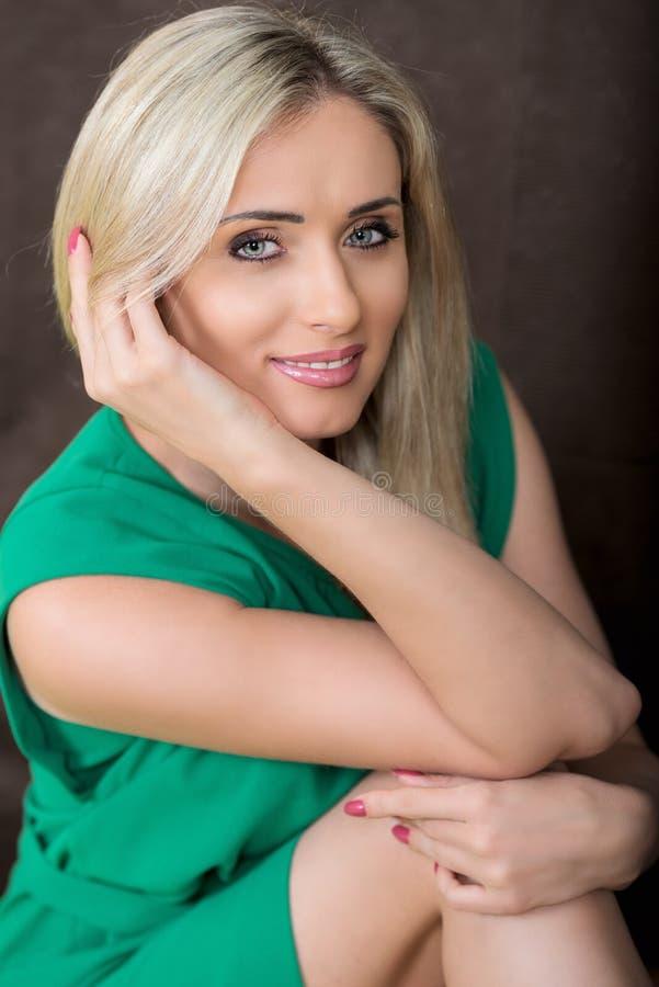 Retrato de la mujer rubia sonriente de los jóvenes en vestido verde imagenes de archivo