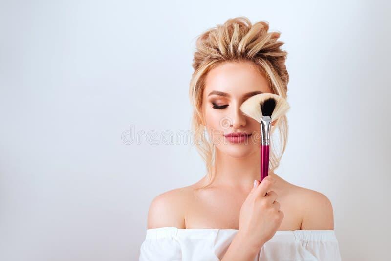 Retrato de la mujer rubia sonriente feliz con el cepillo largo de la tenencia del estilo de pelo ondulado fotografía de archivo