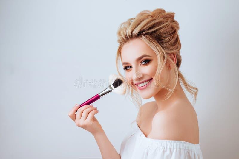 Retrato de la mujer rubia sonriente feliz con el cepillo largo de la tenencia del estilo de pelo ondulado imagenes de archivo