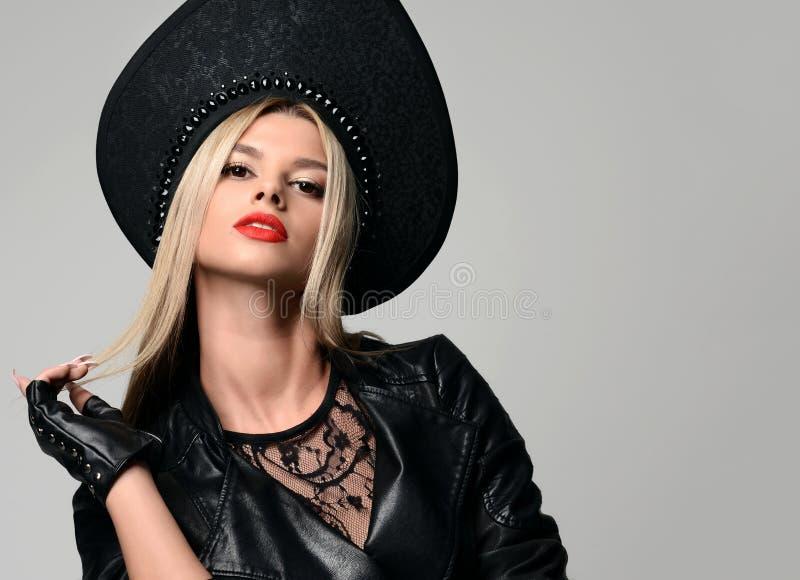 Retrato de la mujer rusa hermosa del pelo rubio del encanto de la alta moda en sombrero moderno en guantes de cuero negros imagen de archivo