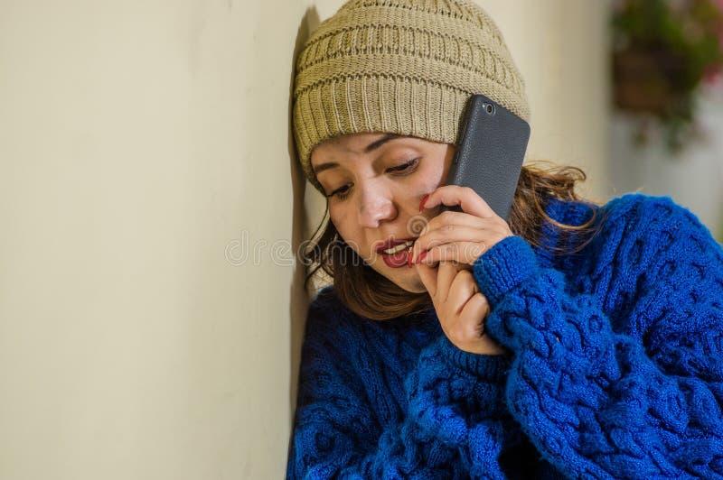 Retrato de la mujer sin hogar sola en la calle en el tiempo frío del otoño que lleva una sudadera con capucha azul y que usa su t imagen de archivo