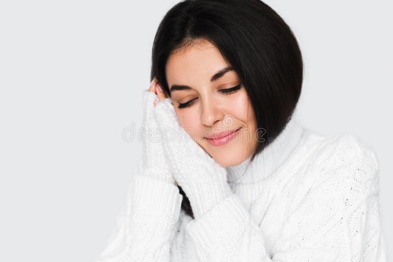 Retrato de la mujer soñadora feliz joven hermosa con los ojos cerrados en el suéter blanco en fondo gris claro Modelo trigueno bo fotos de archivo