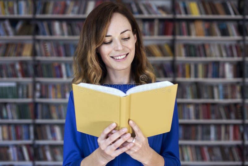 Retrato de la mujer sobre 25 en una biblioteca que lee un libro abierto, concentrado y elegante Estudiante universitario joven en imagen de archivo libre de regalías