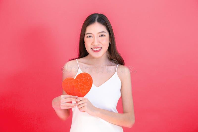 Retrato de la mujer sonriente asiática atractiva que sostiene el rompecabezas rojo del papel del corazón aislado en fondo rosado fotografía de archivo libre de regalías