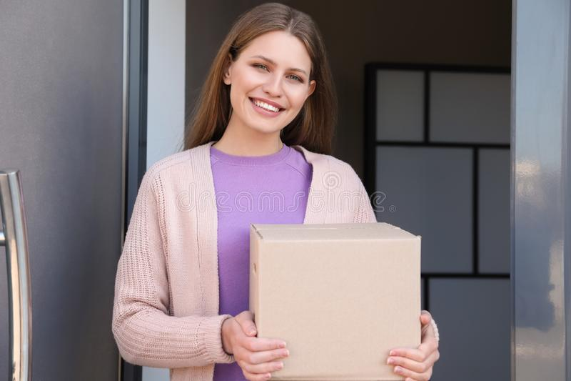 Retrato de la mujer sonriente con el paquete en la puerta Servicio de salida imagen de archivo libre de regalías