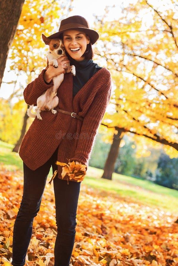 Retrato de la mujer sonriente con el perro al aire libre en otoño imagenes de archivo