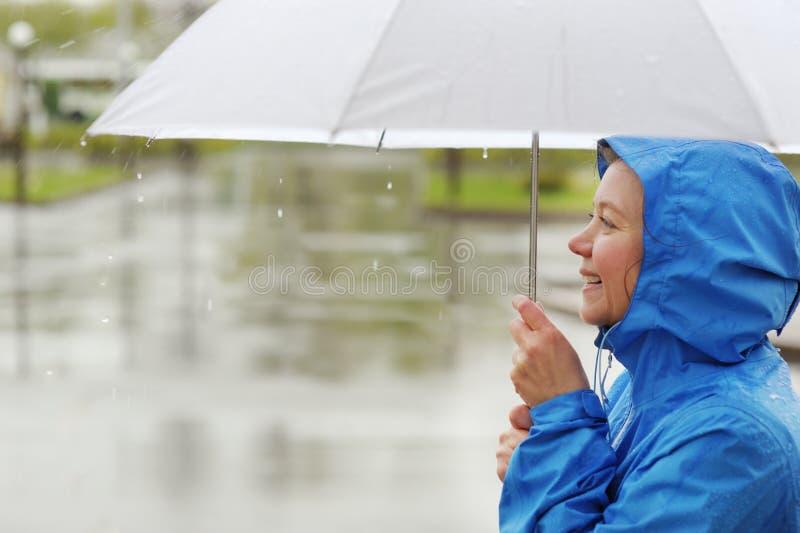 Retrato de la mujer sonriente debajo del paraguas en lluvia fotografía de archivo libre de regalías