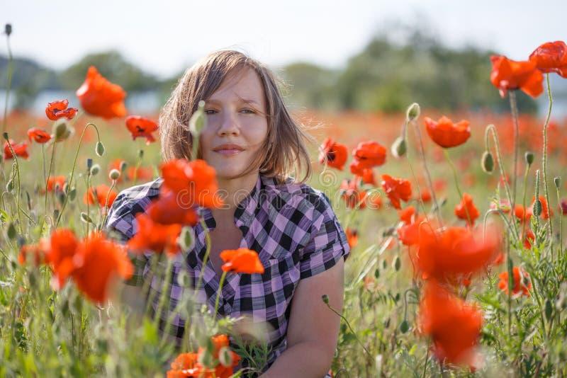 Retrato de la mujer sonriente en campo de la amapola fotos de archivo