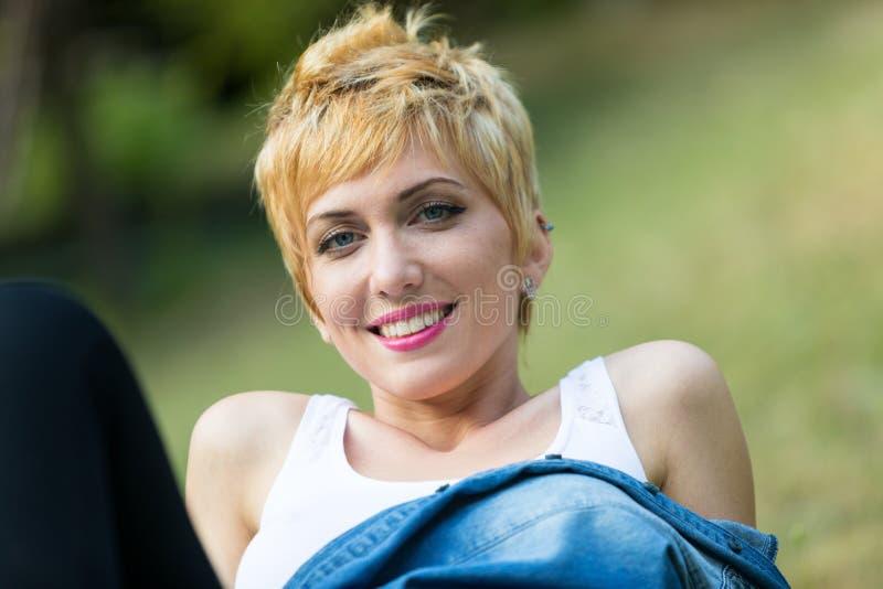 Retrato de la mujer sonriente en la hierba verde fotografía de archivo libre de regalías