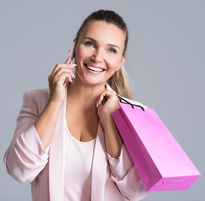 Retrato de la mujer sonriente feliz con el bolso rosado que habla fotografía de archivo