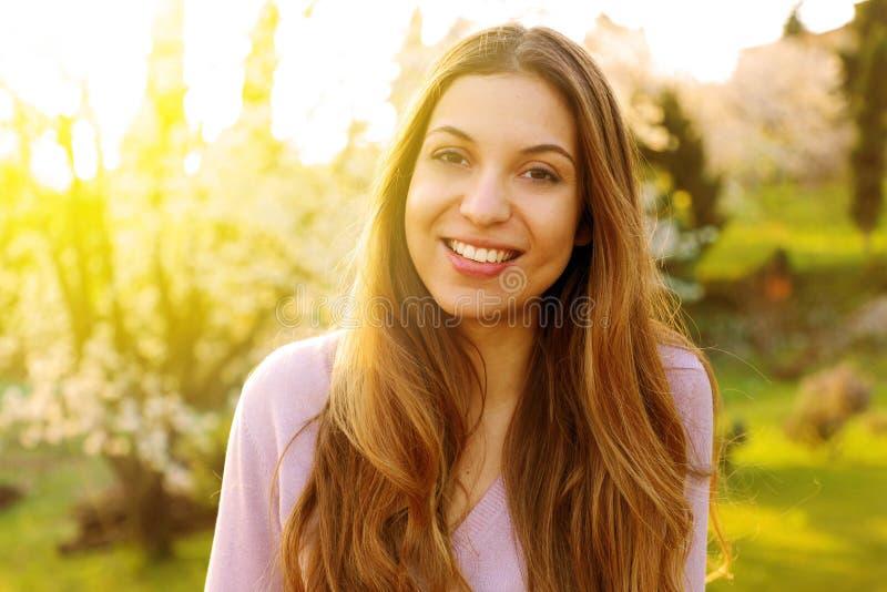 Retrato de la mujer sonriente feliz en verano o día de primavera soleado afuera, mujer sonriente linda que le mira, chica joven a fotografía de archivo