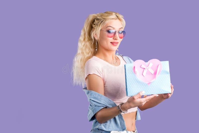 Retrato de la mujer sonriente feliz joven con el bolso de compras aislado sobre el fondo violeta fotografía de archivo libre de regalías