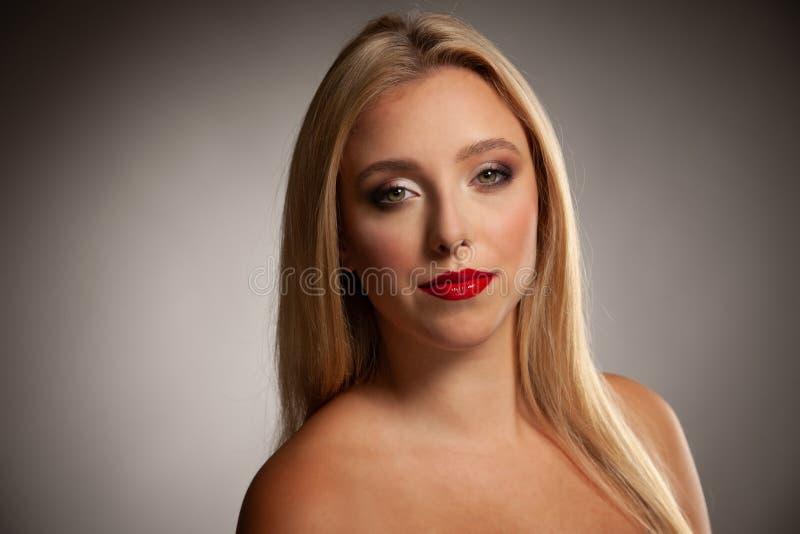 Retrato de la mujer sonriente feliz joven con el brillo azul y rojo de la luz en el pelo foto de archivo
