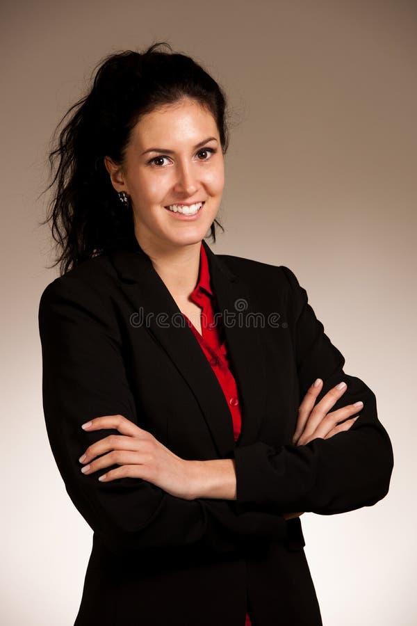 Retrato de la mujer sonriente feliz joven en la situación del traje de negocios sobre fondo gris fotos de archivo