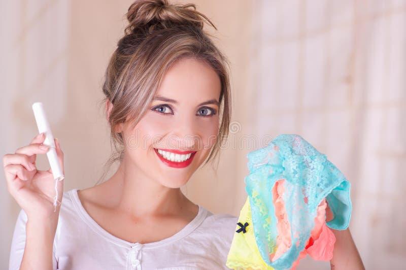 Retrato de la mujer sonriente hermosa joven que sostiene un tapón del algodón de la menstruación en una mano y con su otra mano fotografía de archivo libre de regalías