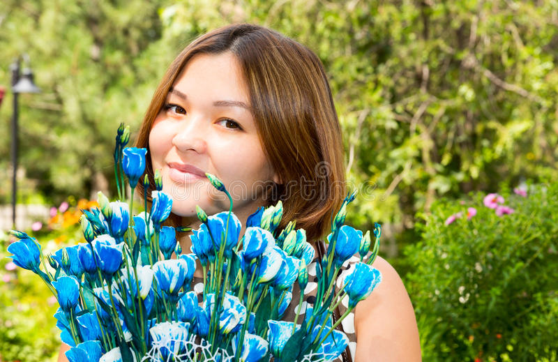 Retrato de la mujer sonriente hermosa joven y de las flores del Kazakh asiático al aire libre imagenes de archivo