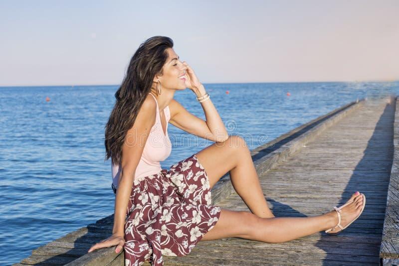 Retrato de la mujer sonriente hermosa que habla en el teléfono que se sienta en un embarcadero del mar foto de archivo