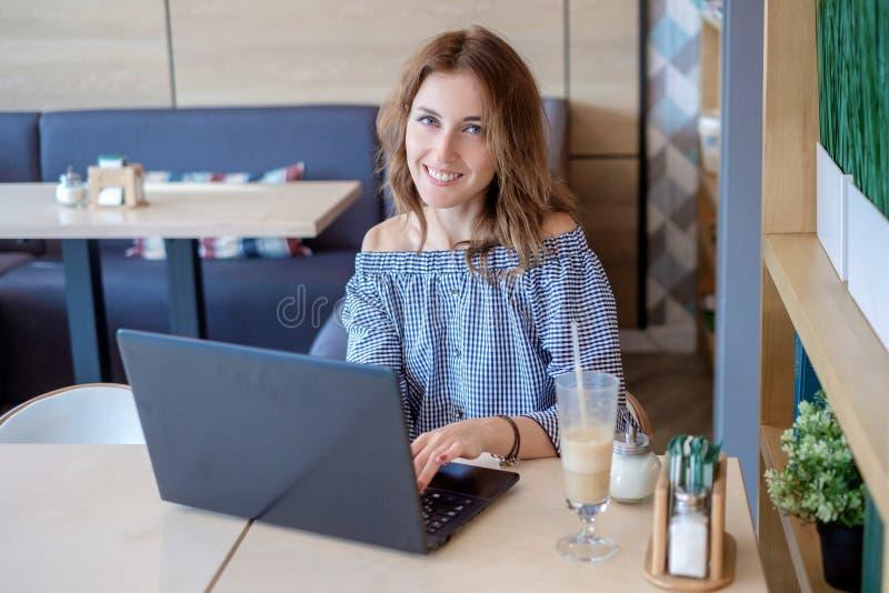 Retrato de la mujer sonriente hermosa que se sienta en un café con el ordenador portátil negro imagen de archivo libre de regalías