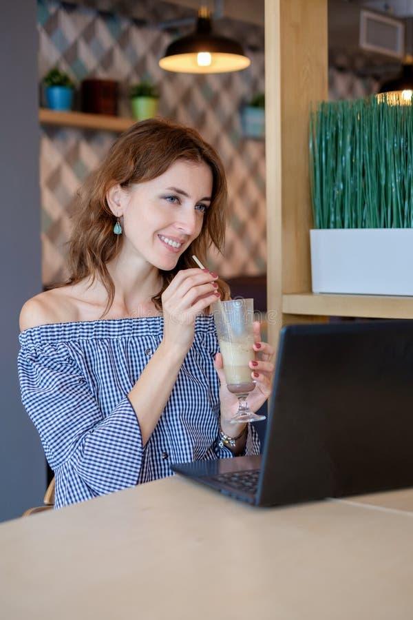 Retrato de la mujer sonriente hermosa que se sienta en un café con el ordenador portátil negro imágenes de archivo libres de regalías