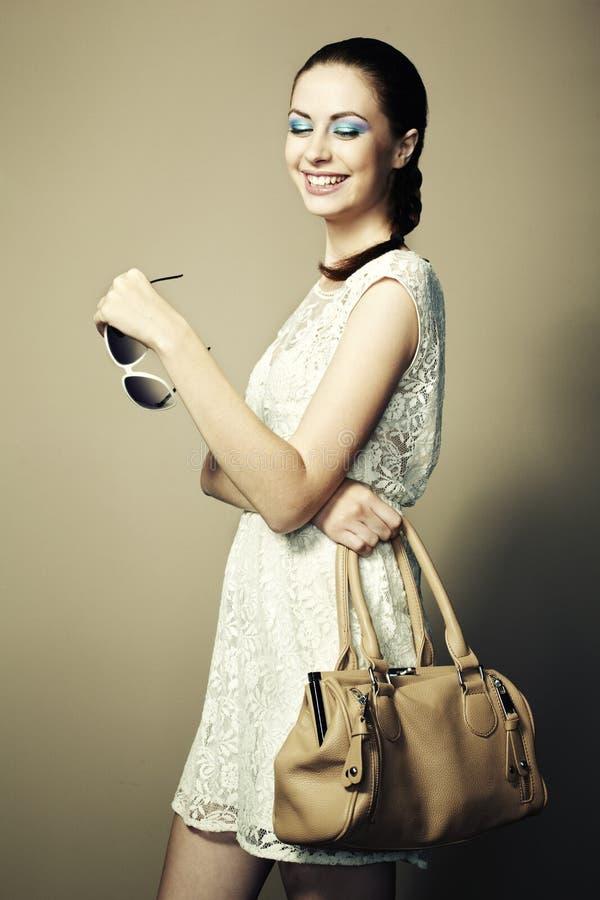 Retrato de la mujer sonriente joven con un bolso de cuero imagen de archivo
