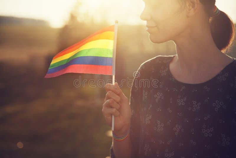 Retrato de la mujer sonriente joven feliz con pulsera de la cinta del arco iris en su mano que sostiene la bandera colorida del a imagen de archivo