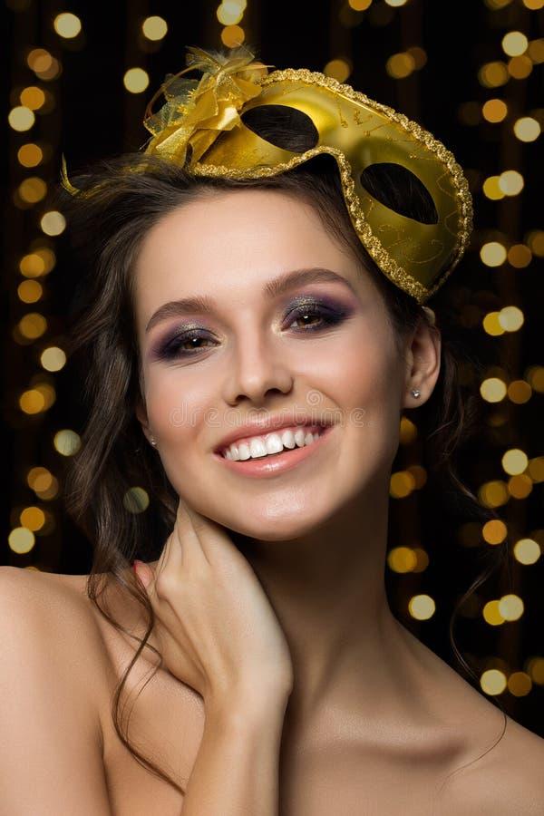 Retrato de la mujer sonriente joven hermosa que lleva el partido de oro m fotografía de archivo