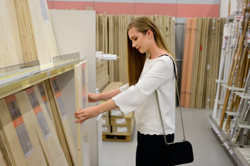 Retrato de la mujer sonriente joven que elige el suelo laminado de madera en tienda foto de archivo