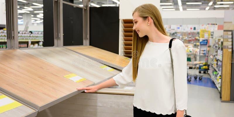 Retrato de la mujer sonriente joven que elige el suelo laminado de madera en tienda fotografía de archivo