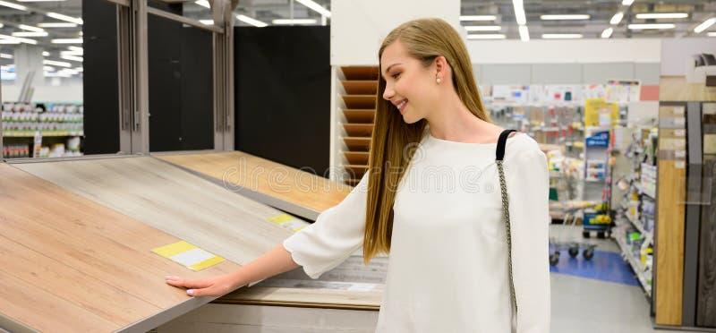 Retrato de la mujer sonriente joven que elige el suelo laminado de madera en tienda imagen de archivo libre de regalías