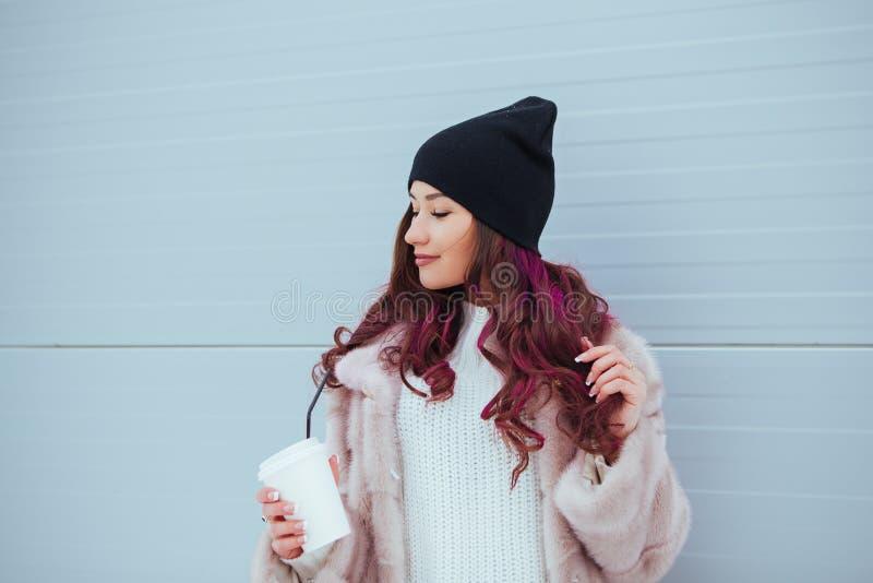 Retrato de la mujer sonriente de la moda de la belleza con café en capa de visión y sombrero negro en fondo rosado outdoor fotografía de archivo