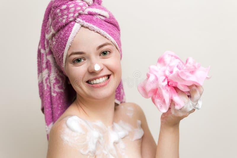 Retrato de la mujer sonriente de la muchacha con el pelo mojado envuelto en la toalla rosada que toma la ducha o el baño con espu fotos de archivo