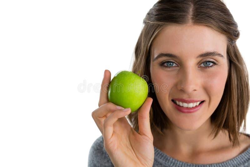 Retrato de la mujer sonriente que sostiene la manzana del granny smith fotos de archivo