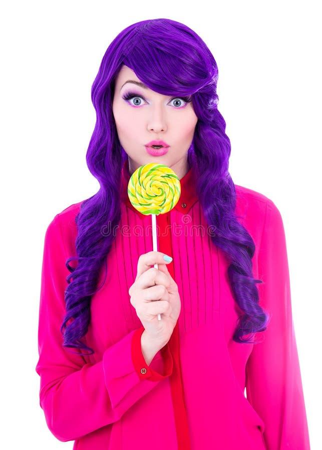 Retrato de la mujer sorprendida con la peluca púrpura del pelo que sostiene colorfu foto de archivo