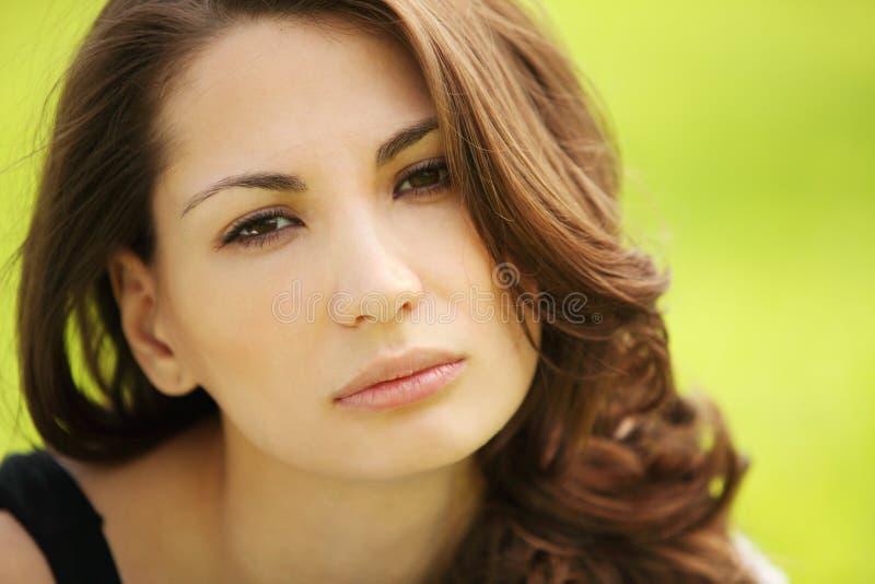 Retrato de la mujer triste joven atractiva hermosa en el verde del verano imagen de archivo