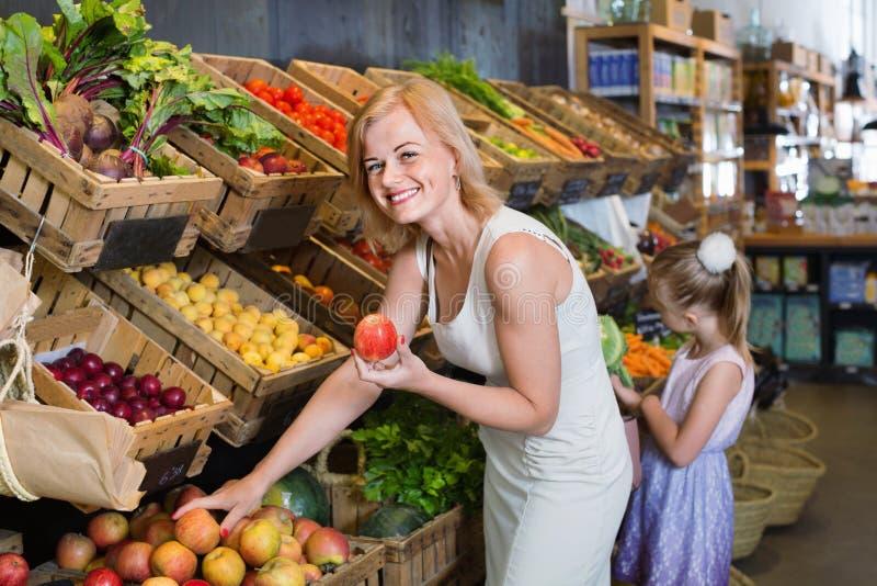 Retrato de la mujer y de la muchacha que compran frutas frescas imágenes de archivo libres de regalías