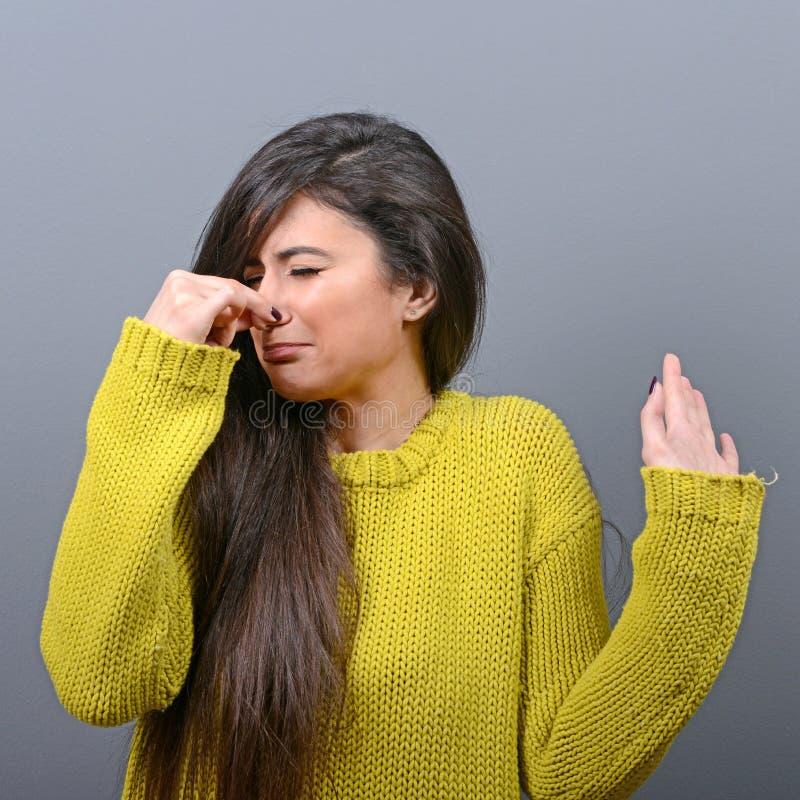 Retrato de la nariz de la cubierta de la mujer con la demostración de la mano que algo apesta contra fondo gris fotografía de archivo