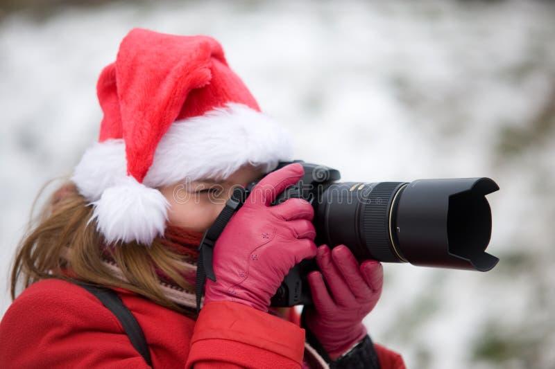 Retrato de la Navidad de una mujer con la cámara de la foto foto de archivo