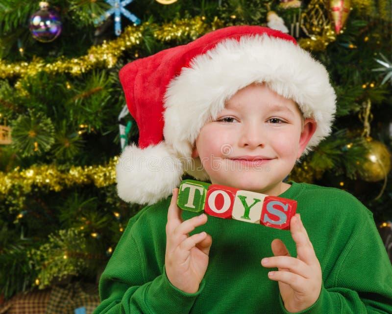 Retrato de la Navidad del niño feliz que lleva el sombrero de Papá Noel delante de bloques de la tenencia del árbol de navidad imagenes de archivo