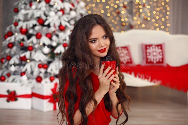 Retrato de la Navidad Muchacha feliz hermosa con la taza Mujer bonita sonriente con el pelo largo y el maquillaje rojo de los lab imágenes de archivo libres de regalías