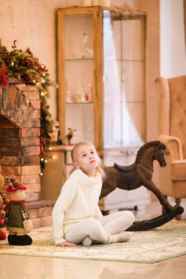 Retrato de la Navidad de la muchacha rubia feliz del niño en el suéter blanco que localiza en el piso cerca del árbol de navidad  fotografía de archivo libre de regalías