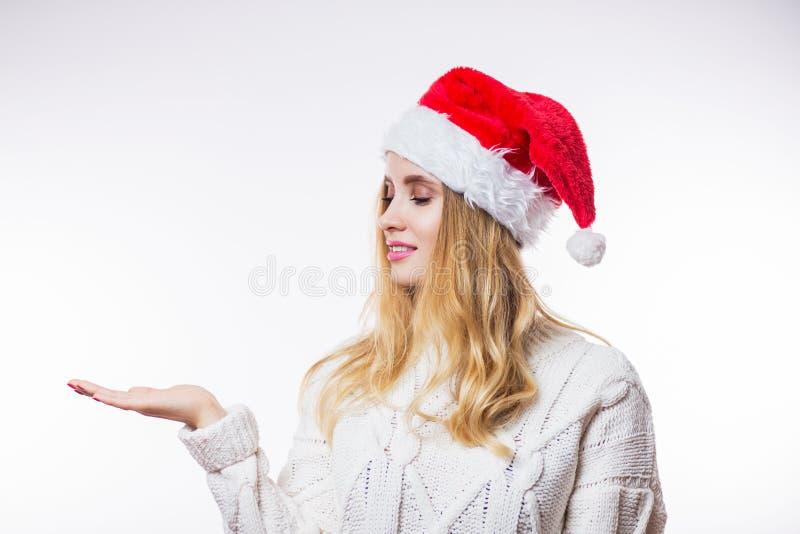 Retrato de la Navidad de la mujer rubia joven atractiva en suéter caliente beige y el sombrero rojo de Papá Noel que muestran su  imágenes de archivo libres de regalías